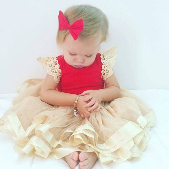 @iylarosejellick wearing a red sleeveless romper with pale gold pixie wings