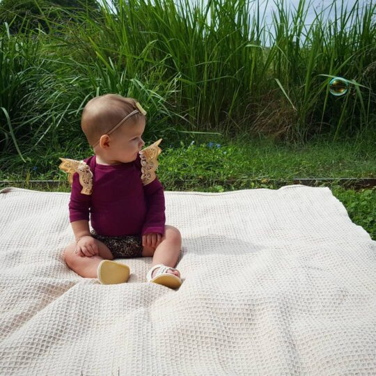 ourlife_withlove waring a wine long sleeve basic bodysuit with pale gold pixie wings